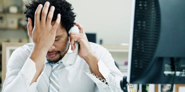 Businessman on phone at desk in office with hand on forehead