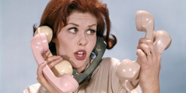 1960s FRUSTRATED YOUNG REDHEADED WOMAN TRYING TO ANSWER HANDLE FIVE TELEPHONE RECEIVERS STUDIO (Photo...