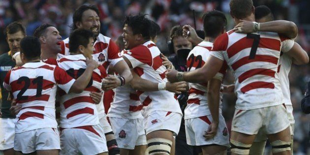 Japan's players celebrate winning the Pool B match of the 2015 Rugby World Cup between South Africa and...