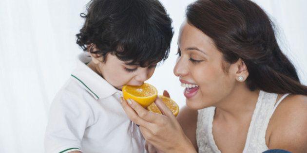 Woman feeding orange to her