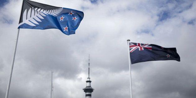 The existing New Zealand flag, right, flies alongside an alternative flag design as the Sky Tower, center,...