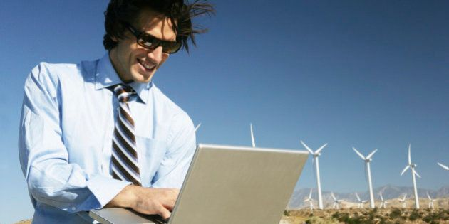 Young businessman using laptop near wind