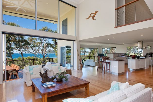 The two-storey home features soaring ceilings and timber