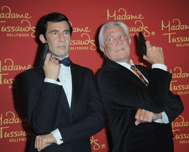 George Lazenby poses with a wax sculpture of his rendition of James