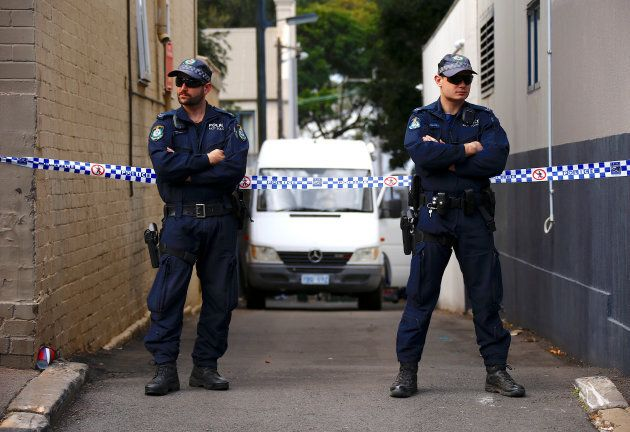 Police officers block a small alley where police vans are parked at a home being searched after Australian...