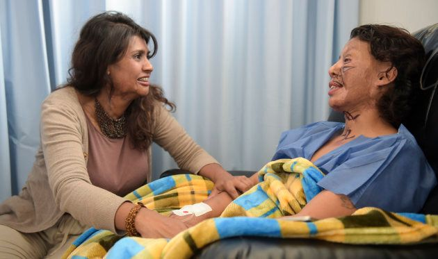 Angeles Borda (R), who survived an acid attack ten years ago, is reassured by Gina Potes, the victim...