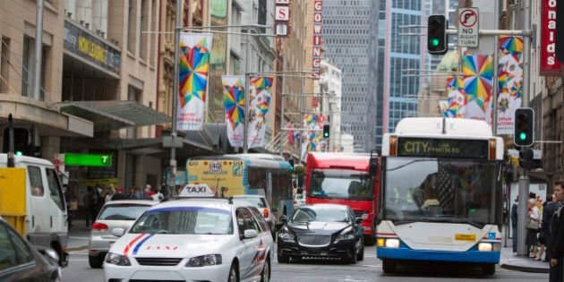 Traffic in Sydney Australia including a taxi and a bus at the intersection of George and King