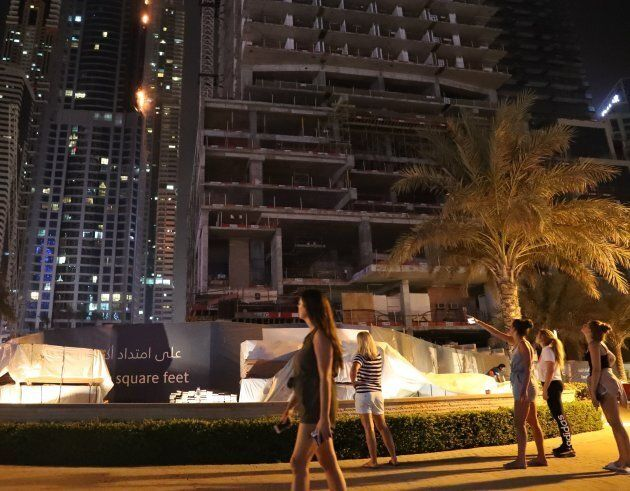 Stunned onlookers watch as one of the world's tallest residential towers is engulfed by