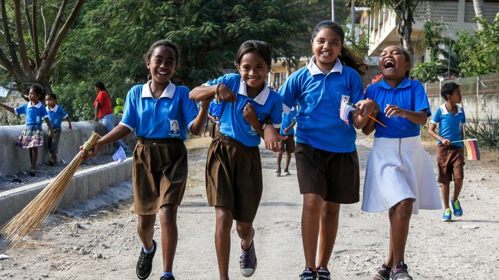 Four school girls laugh and play as they make their way down to the Tour de Timor 2016 finish line. Baucau, Timor-Leste.
