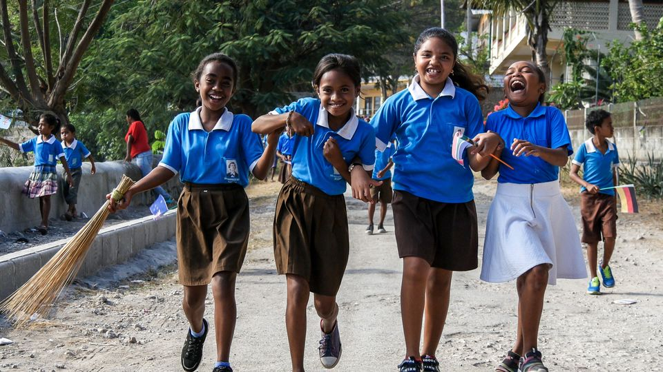 Four school girls laugh and play as they make their way down to the Tour de Timor 2016 finish line. Baucau,