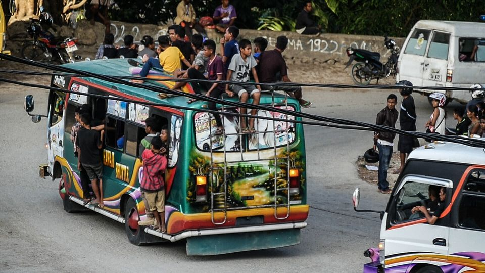 Buses and trucks spill at the sides with passengers. Just your standard form of Transport in Timor. Baucau,