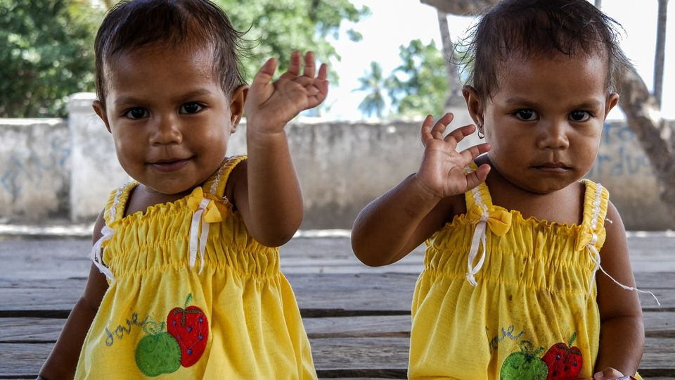 These gorgeous girls look like a mirror image as they wave 'hi' to the camera. Baucau,