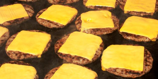 Beef hamburgers cooking on barbecue with melting cheese slice on