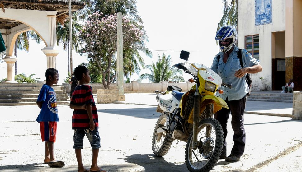 Local Timorese kids check out AUSMAT Paramedic, Peter Jones, motorbike as he finishes his final shift following riders through the hot and rough terrain of Tour de Timor 2016. Baucau, Timor-Leste.