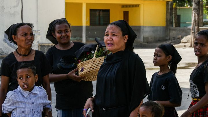 These women gather with their daughters and sons outside of the church at the finish line of Tour de Timor 2016. They wait and watch riders finish before making their way to service. Baucau, Timor-Leste.