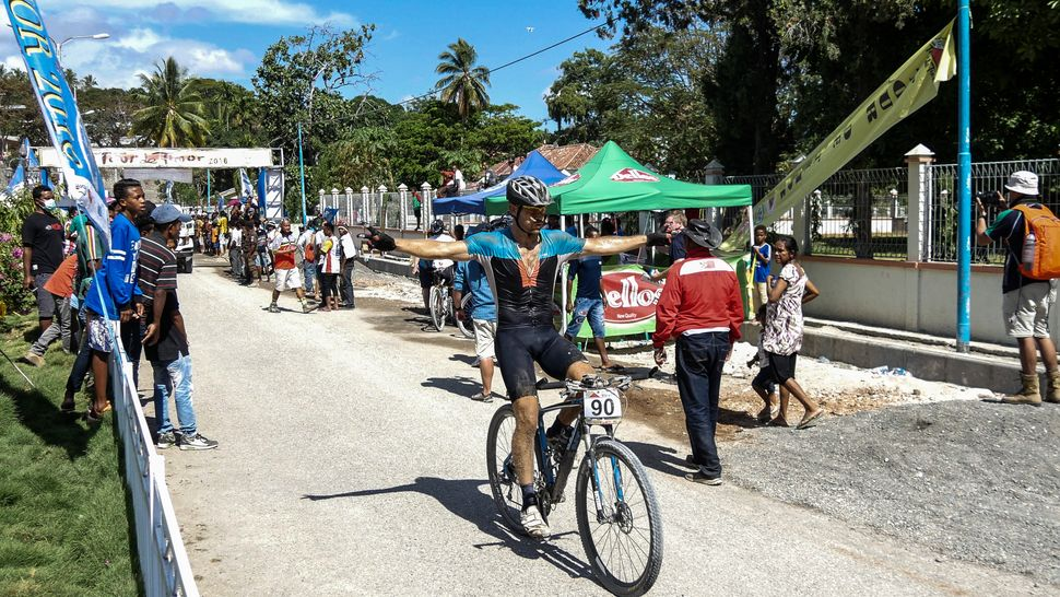 A relieved and spent rider comes through the finish line at Tour de Timor 2016. It's 5 days of rough terrain in hot, tropical climate. Baucau, Timor-Leste.
