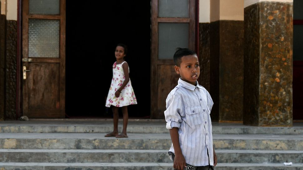 This boy is transfixed on the finish line as his sister calls him into church. Baucau, Timor-Leste.