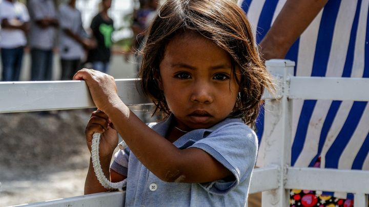 This little man waits patiently at the finish line of Tour de Timor 2016. The race brings a new town to life each day it passes through the 5 stages. Baucau, Timor-Leste.