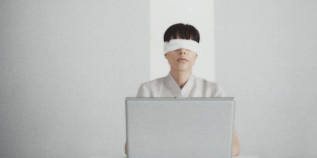 Blindfolded woman sitting behind