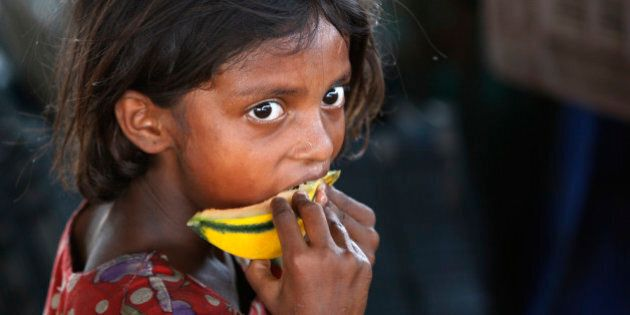 FILE - In this Friday, June 12, 2015 file photo, an Indian child laborer eats a piece of a muskmelon...