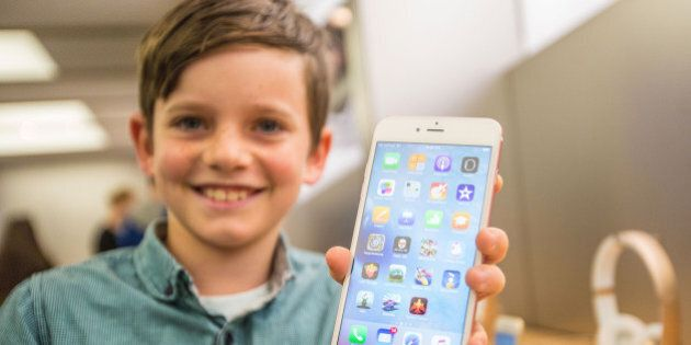 SYDNEY, AUSTRALIA - SEPTEMBER 25: Levi aged 10, shows of the new iPhone 6s Plus in rose gold as crowds...