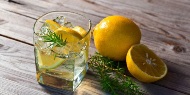 alcoholic drink with lemon and ice on a old wooden