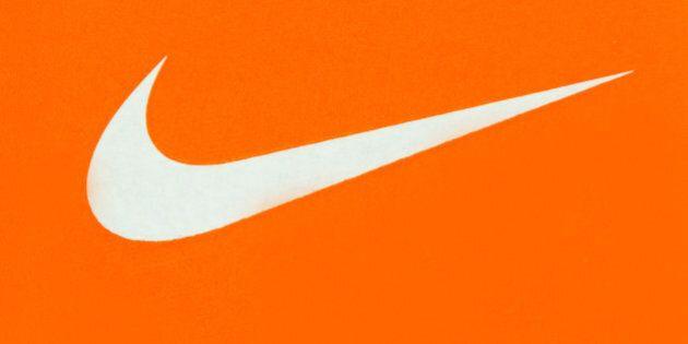TORONTO, ONTARIO, CANADA - 2015/03/29: White Nike Logo on Orange Background;Nike, Inc. is an American...