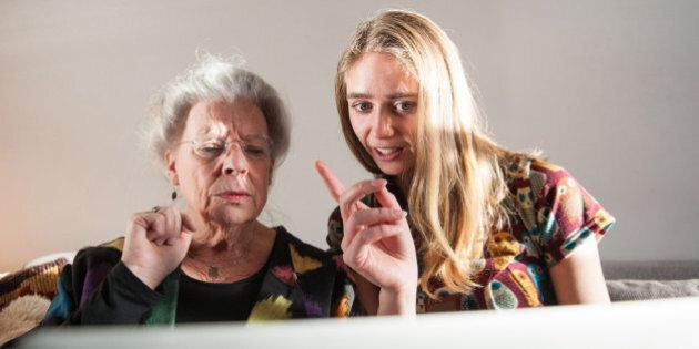 Senior woman and granddaughter sitting on sofa with laptop. The girl is teaching the grandmother how it works.