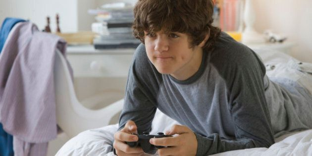 Teenaged boy playing video