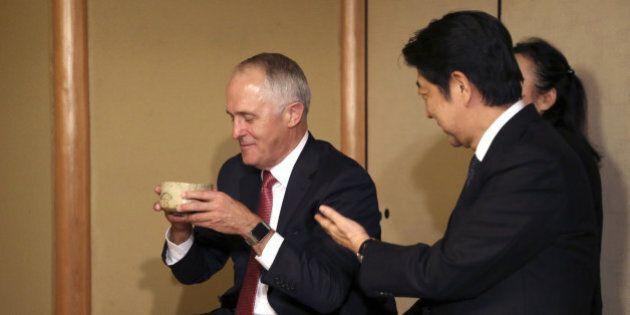 Australian Prime Minister Malcolm Turnbull (L) and Japanese Prime Minister Shinzo Abe (R) attend a tea...