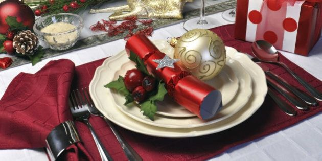 Modern and stylish Christmas dinner table setting including plates, glasses and placemats, bon bons and...