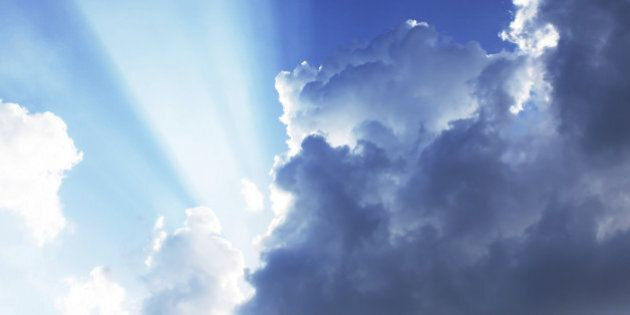 Dramatic blue sky with sun rays bursting through the clouds