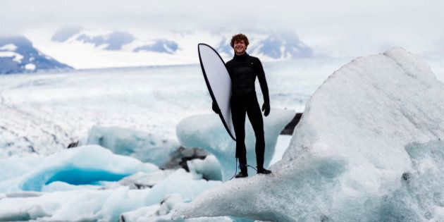Caucasian surfer carrying board near glacial