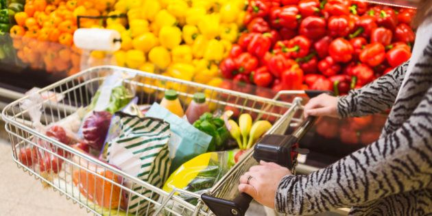 Midsection of woman pushing groceries in shopping cart at