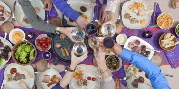 high angle view people toasting over dining table with seafood and meat to grill and on plates with various...