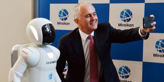 Australian Prime Minister Malcolm Turnbull (R) takes a selfie with Japanese auto giant Honda Motor's...