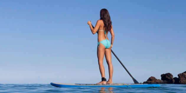 A woman stand-up paddling,
