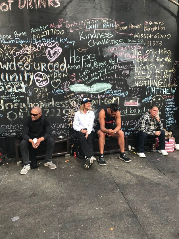 A group of men take in the day under a wall opposite the tent settlement on Martin Place. The six month...