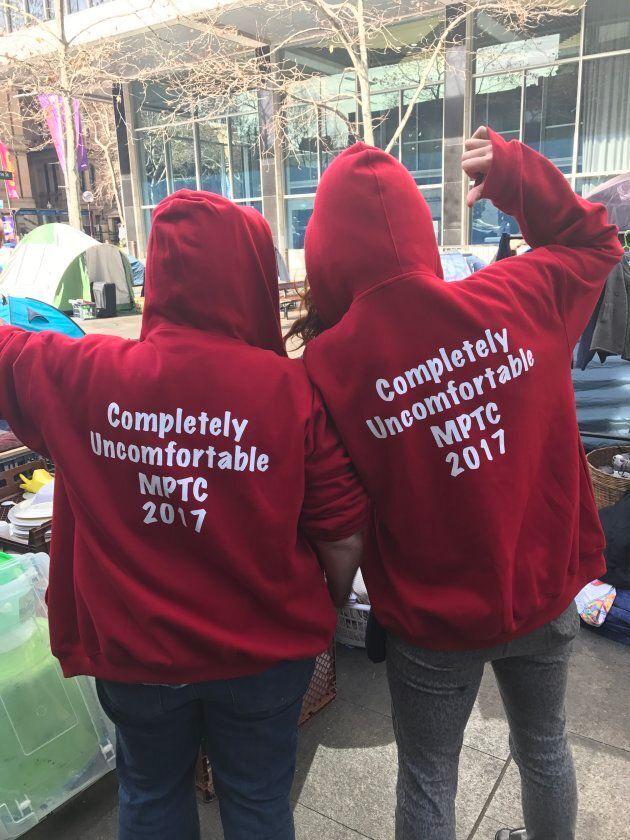 Volunteers Ursula Da Silva (R) and Donna Bartlett (L) wear shirts poking fun at Premier Gladys Berejiklian...
