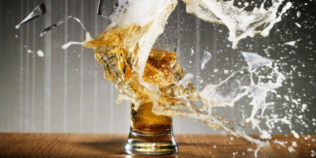 Glass of beer shattering on table