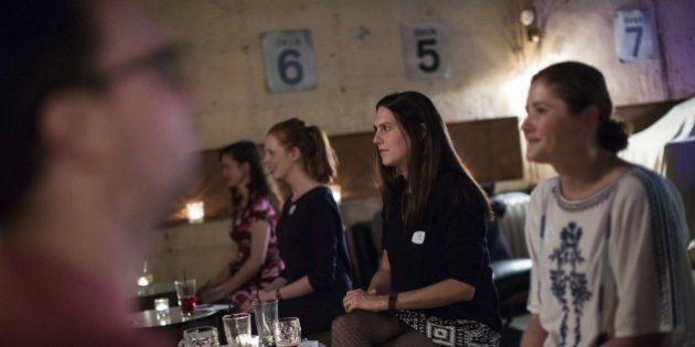 TO GO WITH AFP STORY BY EDOUARD GUIHAIRE Men and women take part in an evening of silent speed dating in a bar in east London on September 23, 2015.  Candles and languid electro-jazz set the scene for a romantic rendezvous at a north London bar, where participants begin the evening with a warm-up of non-verbal flirting games but the couple sitting face-to-face can use only their eyes to beguile. The 90-second silent date is the latest attempt by Londoners to reinvent the city's intoxicating world of nightclubs, bars and fleeting liaisons.  AFP PHOTO / JACK TAYLOR        (Photo credit should read JACK TAYLOR/AFP/Getty Images)