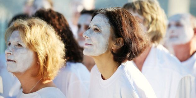 Demonstrators from the environmental group Greenpeace paint their faces white to highlight coral bleaching...