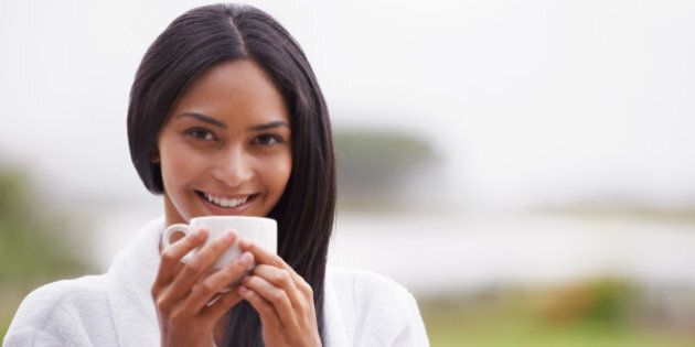 A beautiful young woman enjoying a cup of coffee while wearing a