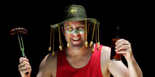 An Aussie man in a cork hat smiles at the camera holding up a sausage on a fork in one hand and a beer...