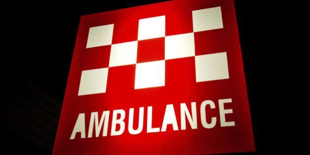 Australian Ambulance sign illuminated at night. Background is pure black and easily