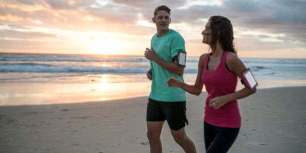 Young couple running on the beach at early morning hours.