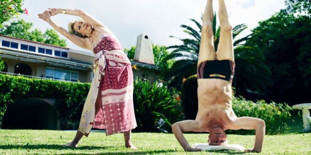 Senior couple performing yoga on lawn, man doing headstand