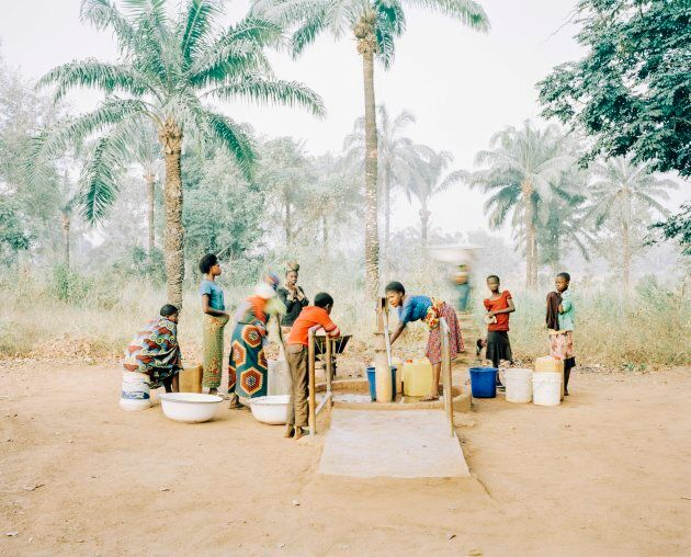 The water pump in Osukputu, Benue, Nigeria -- women and children gather at a hand pump which serves the community of 800 people with clean, safe water.