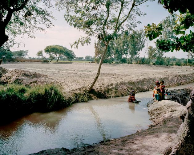 Without access to a clean water supply, people often resort to open sources for all their basic needs such as drinking and washing. Women and children are seen here bathing in an open steam, but this water is always a health risk; in many cases, it proves deadly.