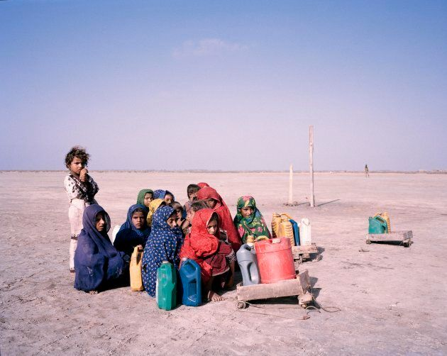 Children pause during their journey to collect water,  huddling together against the wind in southern Sindh. Floods gripped the country in 2010 and 2011, leaving behind only barren land. Agriculture in the region was devastated.